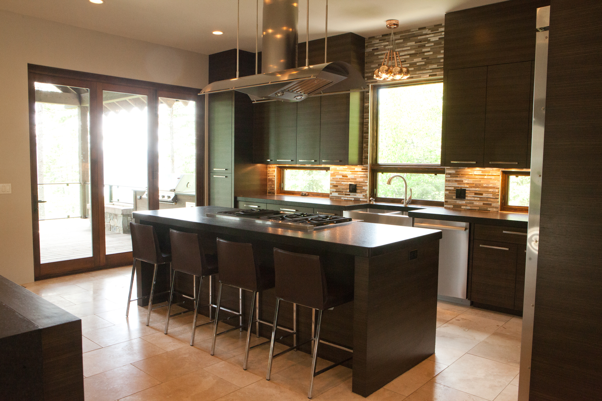 Kitchen of stone and wood. Backsplash with a view to the surrounding woods.